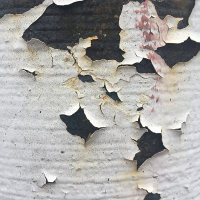 Cracked and peeling white paint on dark surface