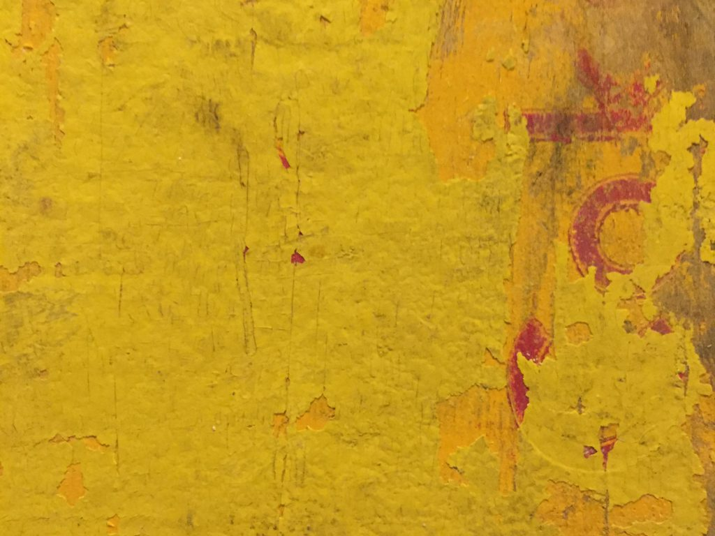 Layers of chipping yellow paint on wood crate