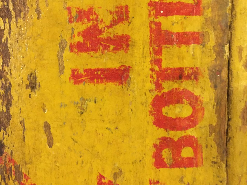 Yellow and red paint on old wood coke crate