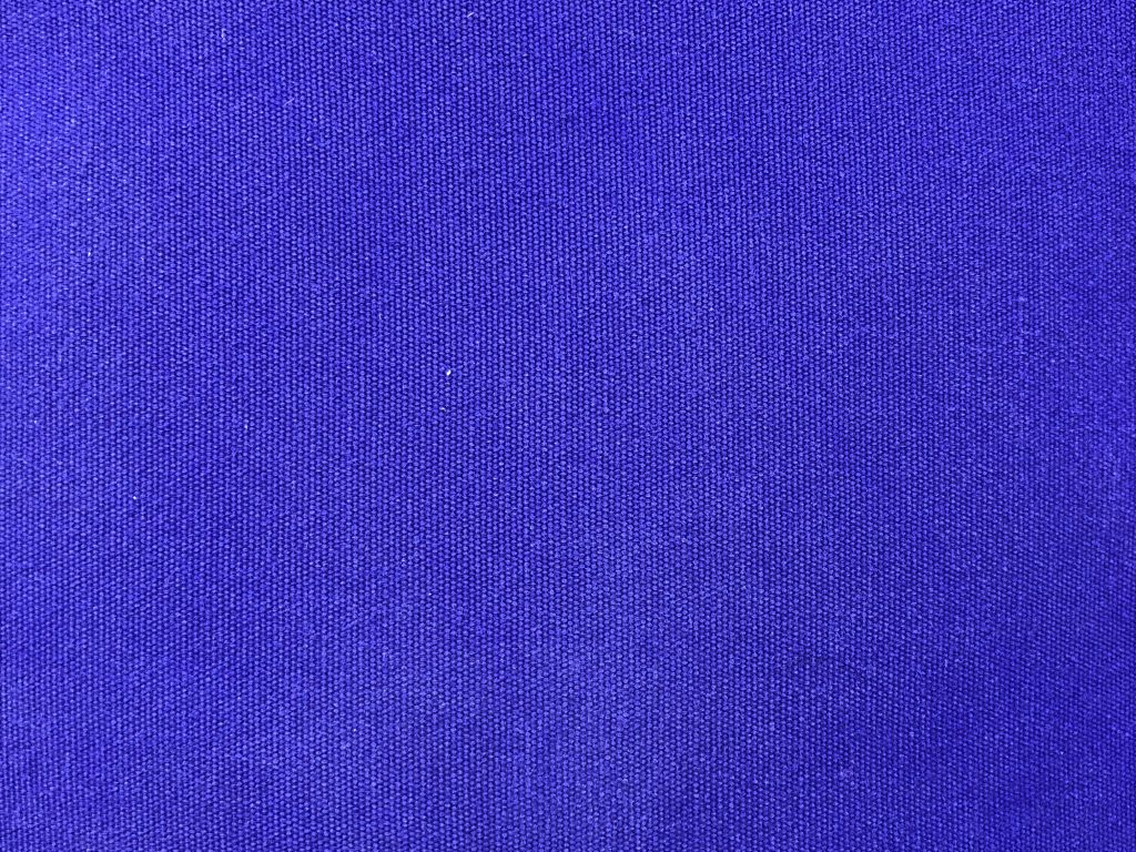 Straight on shot of purple fabric with next knit texture