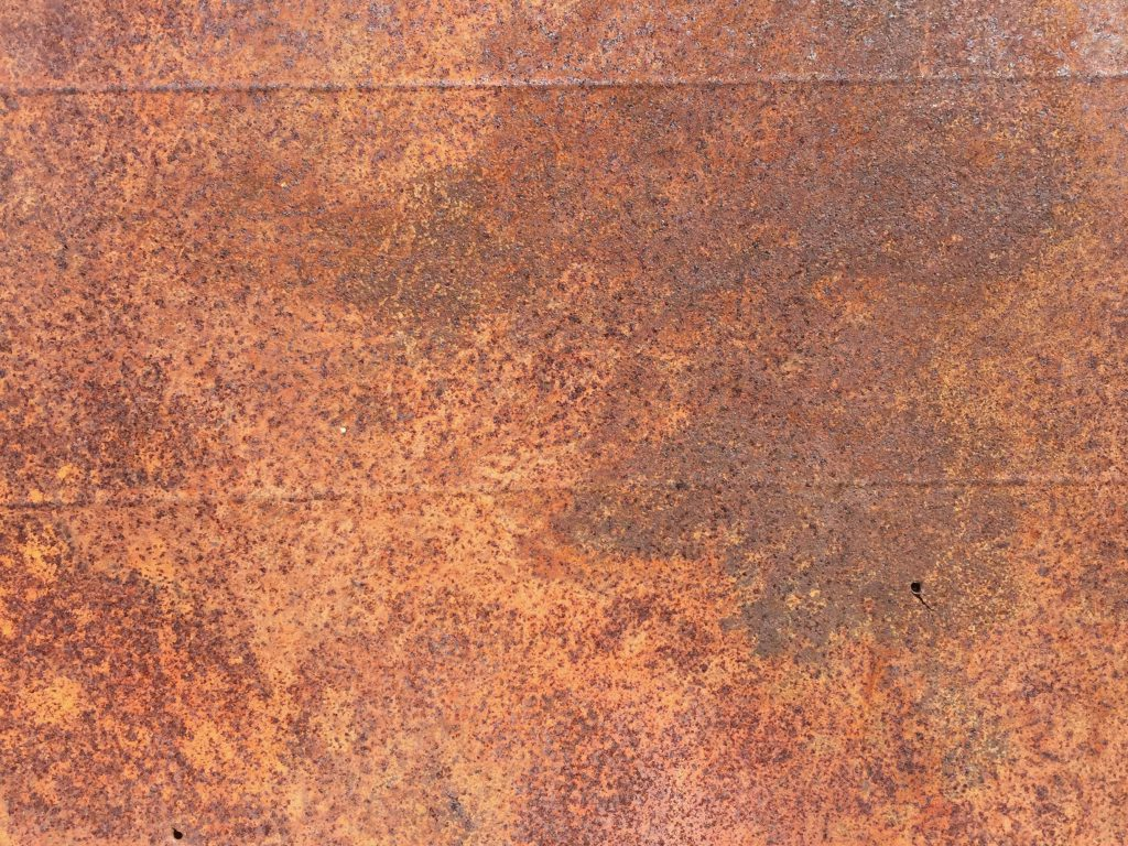 Spotty rust covering entire surface of wall