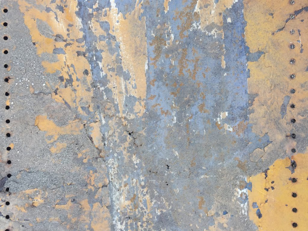 Flaking yellow paint on hard metal