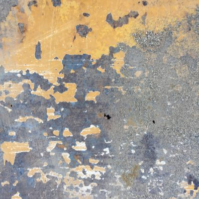 Chipping yellow paint on dark metal