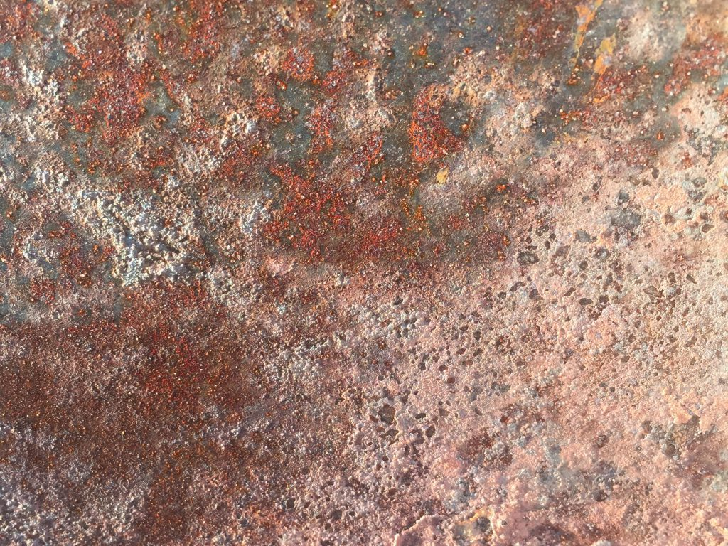 Pink corrosion covering rough rust