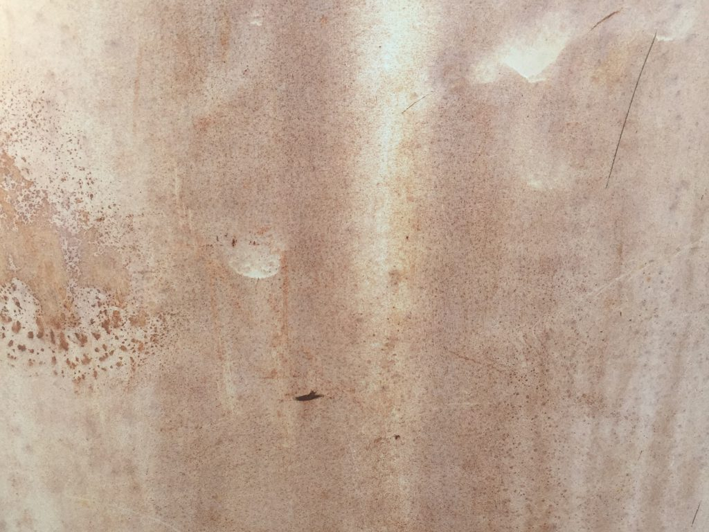 Light white layer of paint over brown metal
