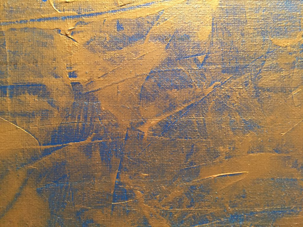 Gold paint over bright blue with canvas texture showing through