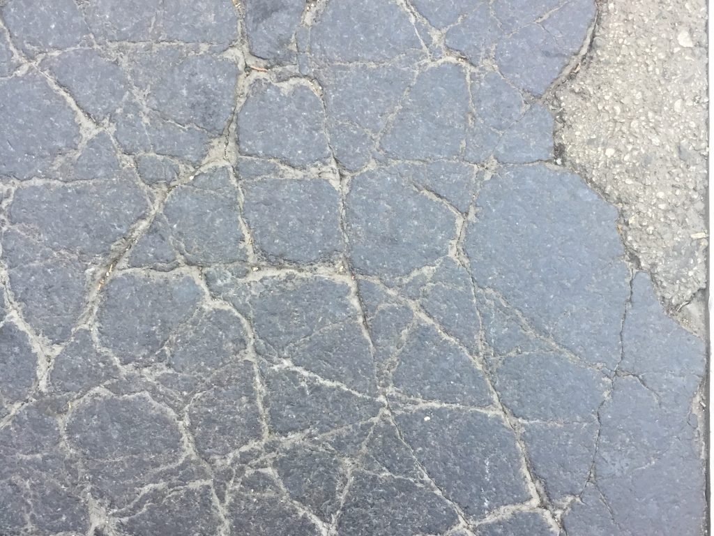 Cracked asphalt with chunk of concrete