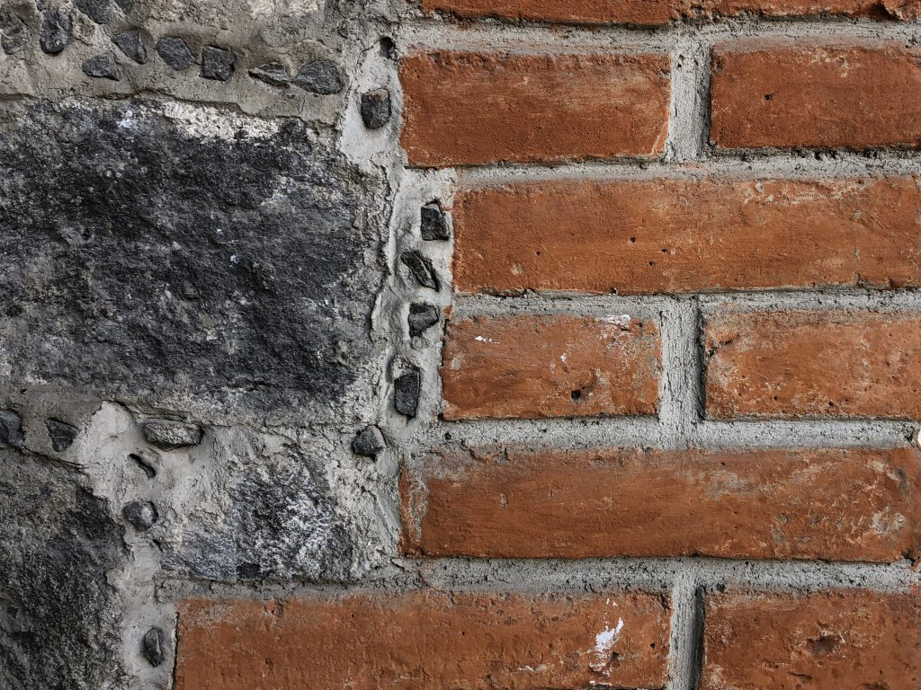 Red brick wall with stone patched area on left