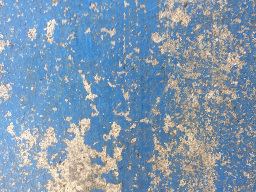Light colored concrete with chipping blue paint