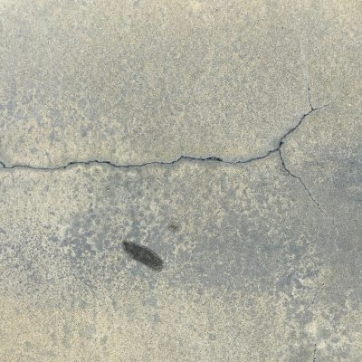 Concrete with light brown overlay and splintering cracks