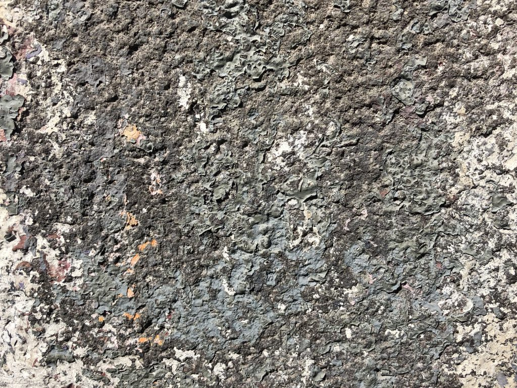 Dark grey concrete covered in paint chips