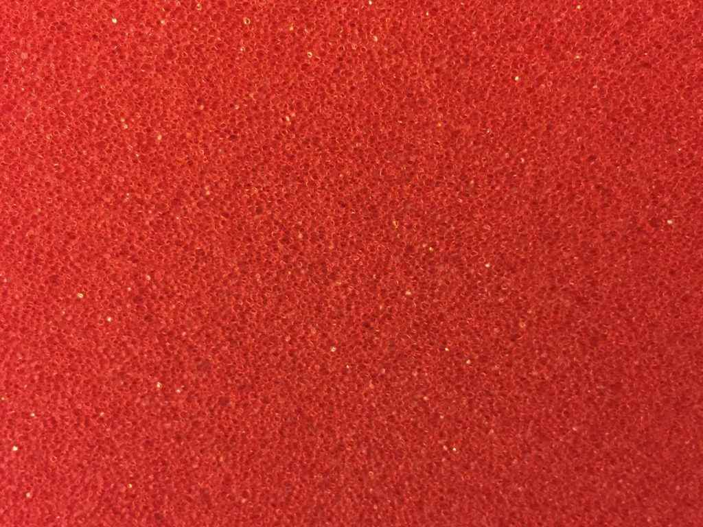 Red plastic texture close up with specs of dark, mid and specular highlights