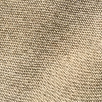 Light brown fabric texture close up with wavy stitching pattern throughout