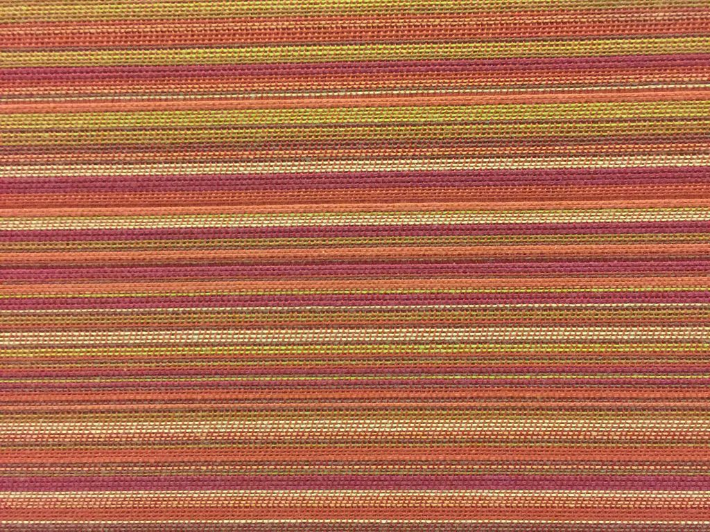 Upholstery with color lines running horizontally varying in width and detailed stitching texture