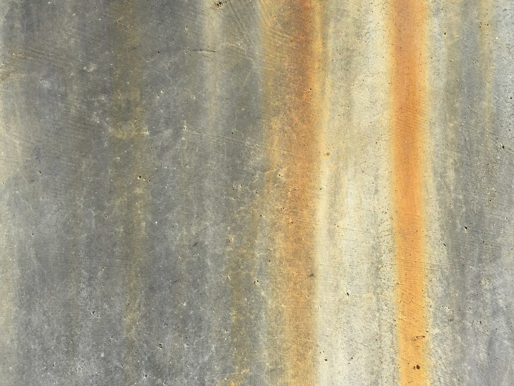 Grey cement face with rust colored streaks running vertically