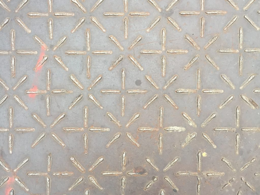 Steel utility cover with pattern of stars and plus symbols welded to top