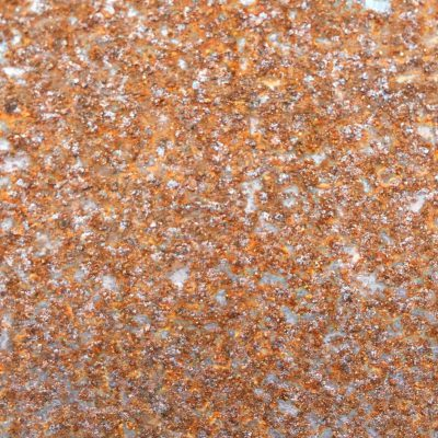 Rough metal texture full of bright brown rust and bits of silver metal shining through
