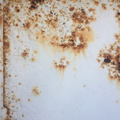 Bright white paint stained with red-brown rust seeping through layers of paint