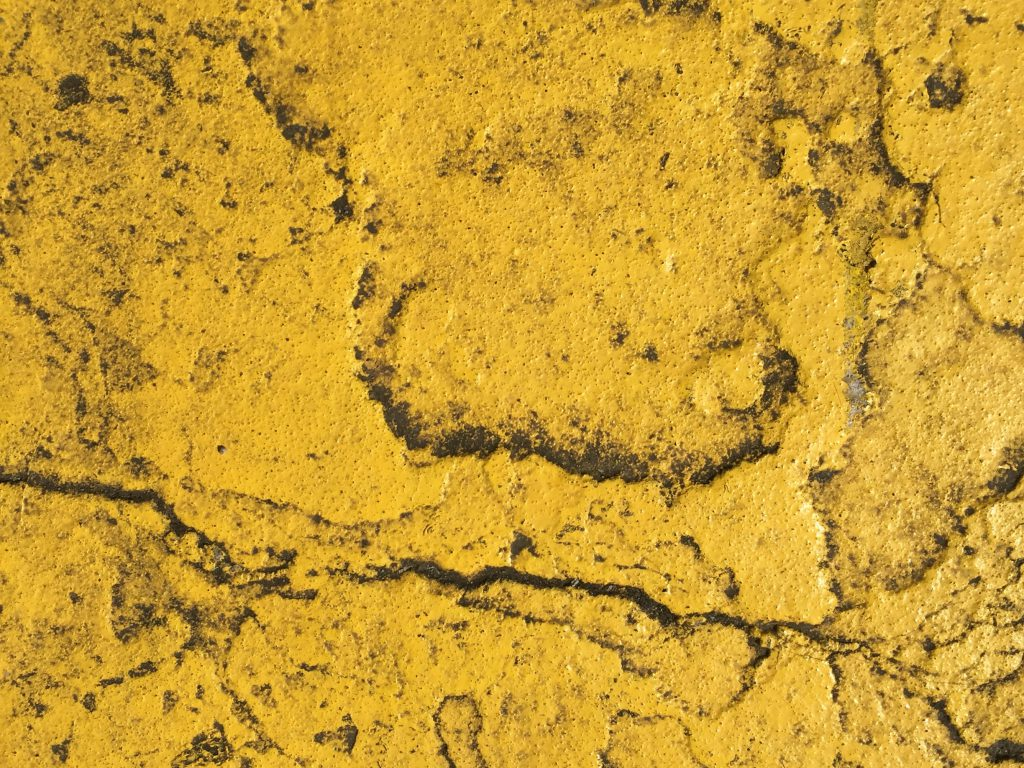 Layers of yellow paint on a concrete street with a layer of filth on top