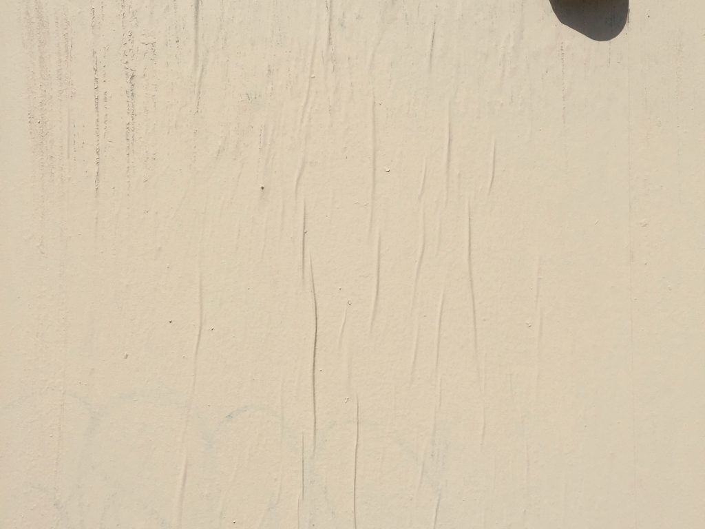 Egg shell white wall with layer of paint over top of paper wrinkles and curling edge