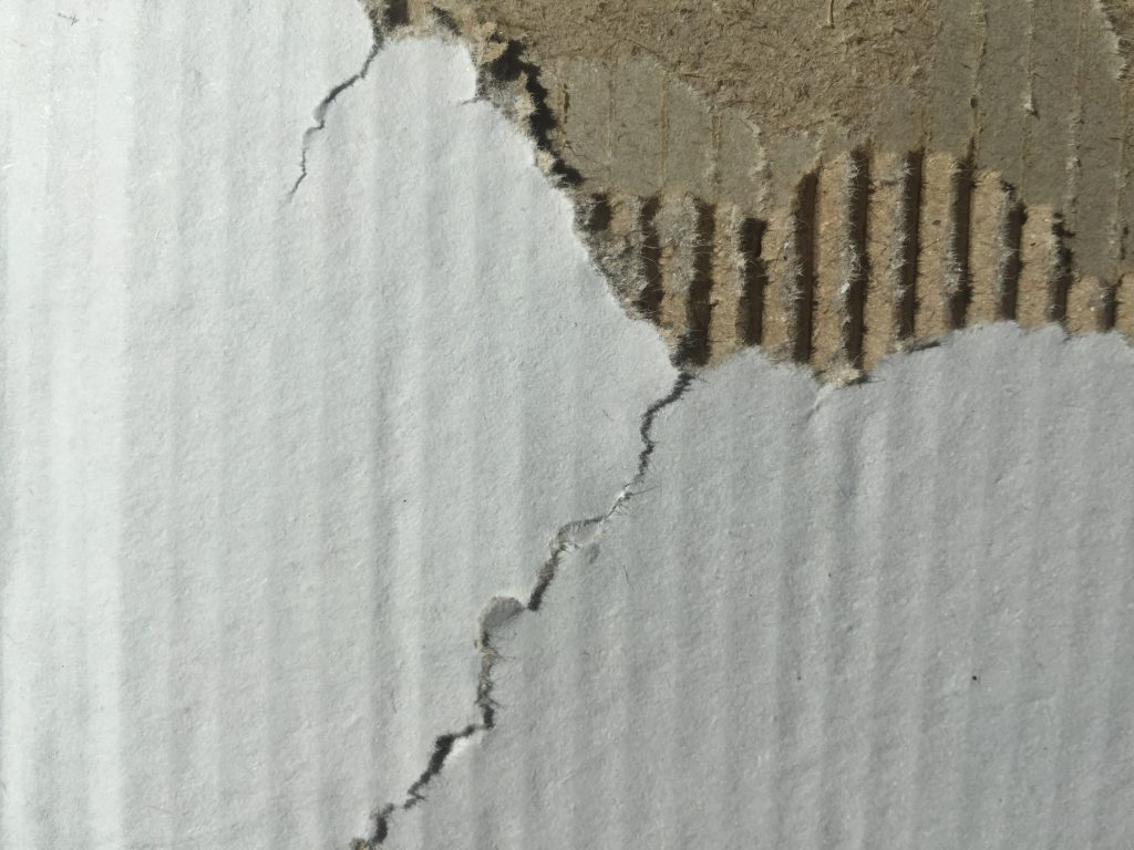 Corrugated cardboard with tears revealing layers insde