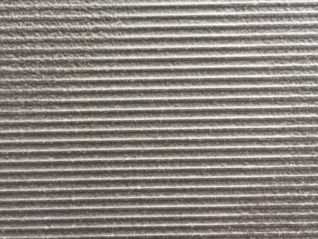 Close up of wall paper with embossed lines moving left to right