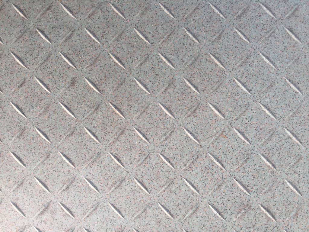 Plastic tile with diagonal indents with tiny dotted texture