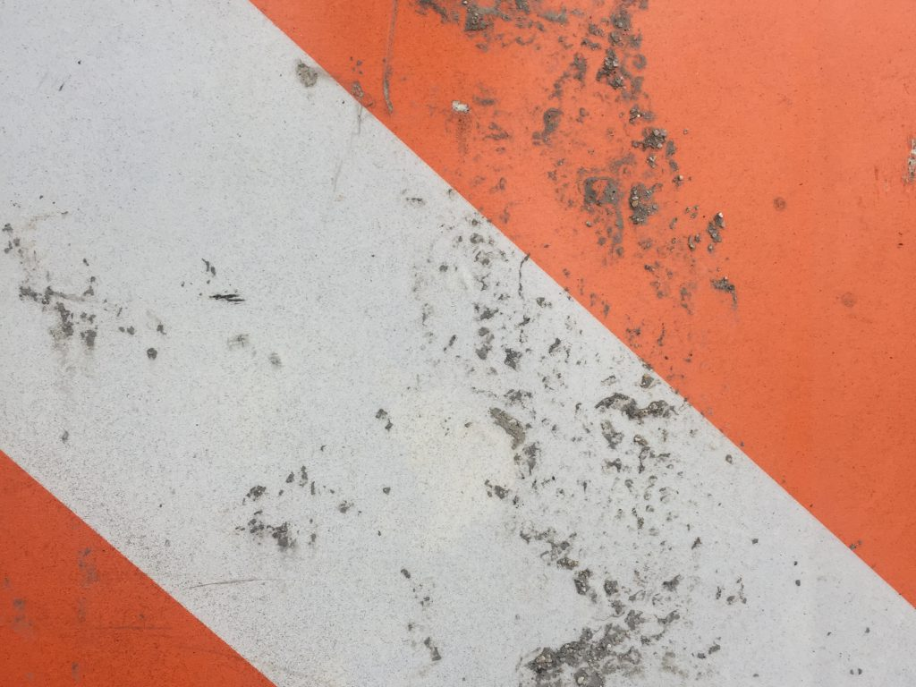 Deep orange and off white street sign with dirty texture clumps