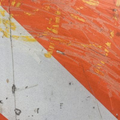 Grunge and heavy scratches on orange and white street sign