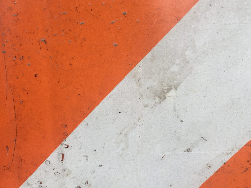 Diagonal color blocks alternating orange and red with rough and dirty texture