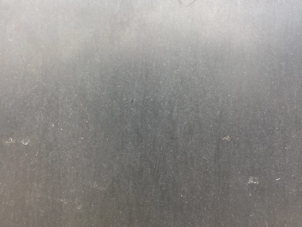 Grey plastic wall with lots of dirt and speckled texture