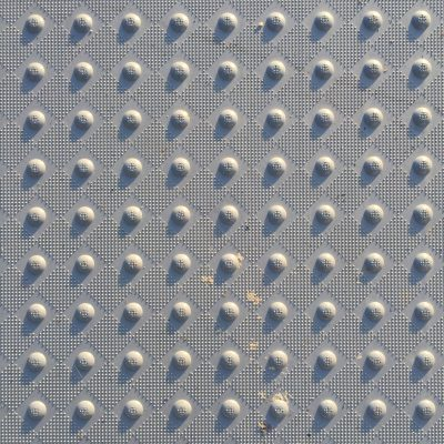 Checkered pattern of small bumps with larger knobs in-between on hard plastic surface