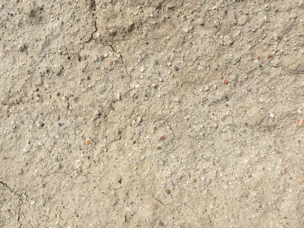 Tiny fractures in light brown dirt