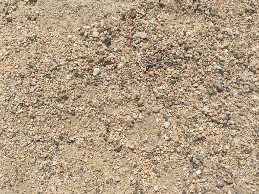 Pebbles and small rocks embedded in light brown dirt