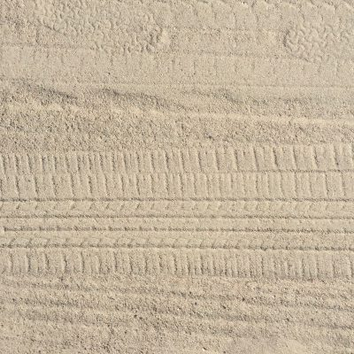 Light brown sand beach with tire marks