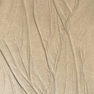 Grooves in wet sand created by tide