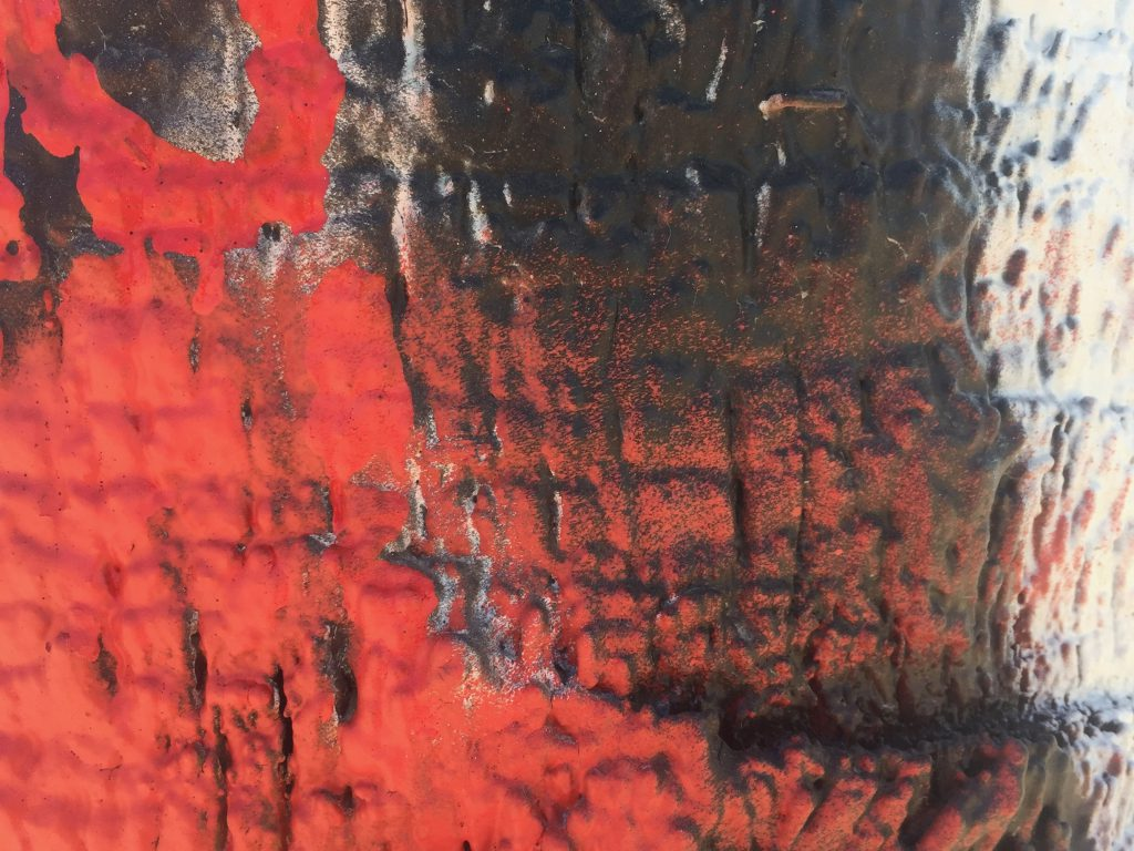 Vibrant red paint on palm tree bark