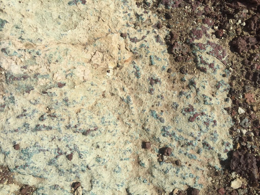 Rocky surface with deep brown base sharply contrasted by blue-white top layer
