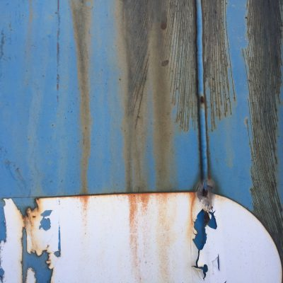 Dull blue paint with rust seeping through cracked paint