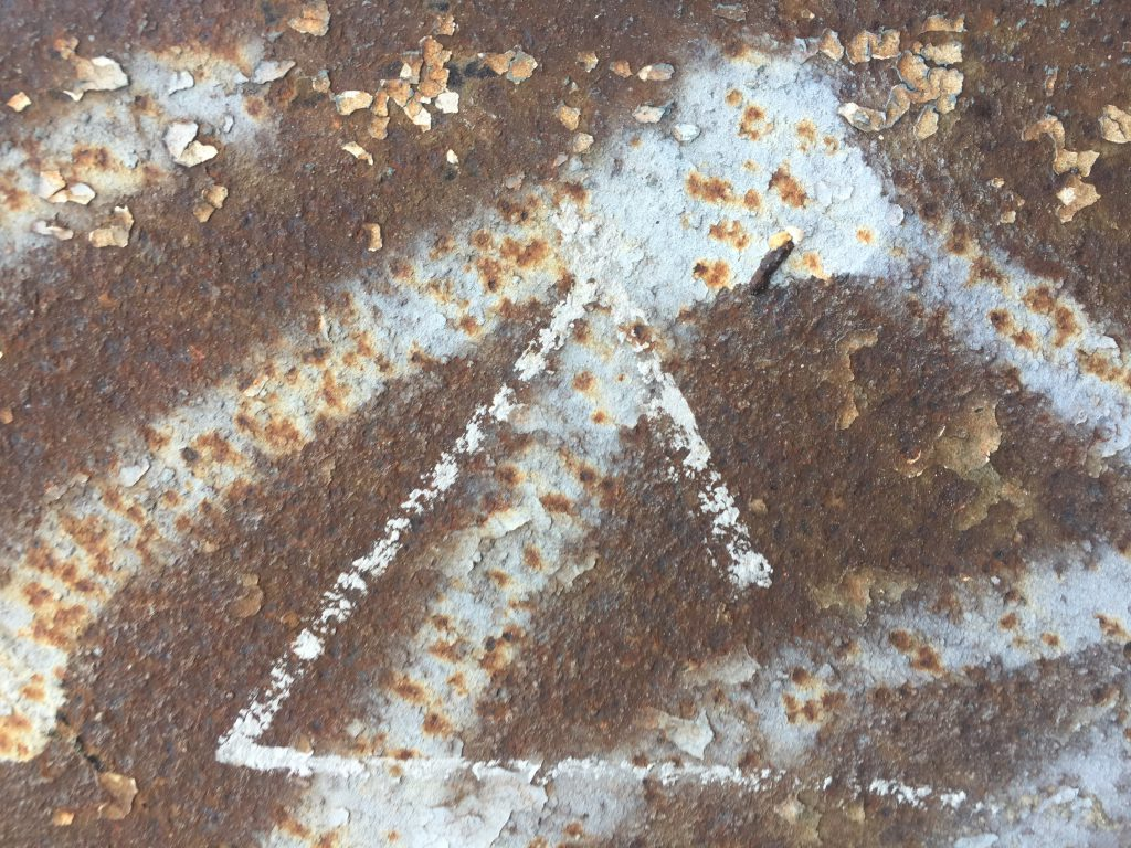 Flaked rusted metal plate with white graffiti