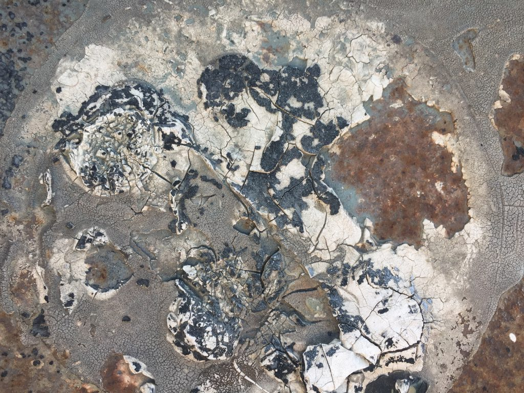 Tar and white paint covering rusted metal