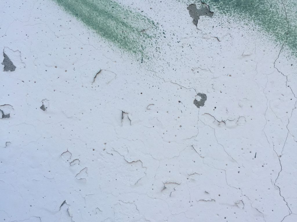 Chipping and cracking white paint on wall