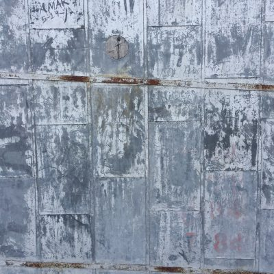 Grey/blue scuffed up metal wall