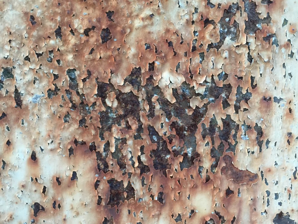 Weathered chipping paint with rust below texture
