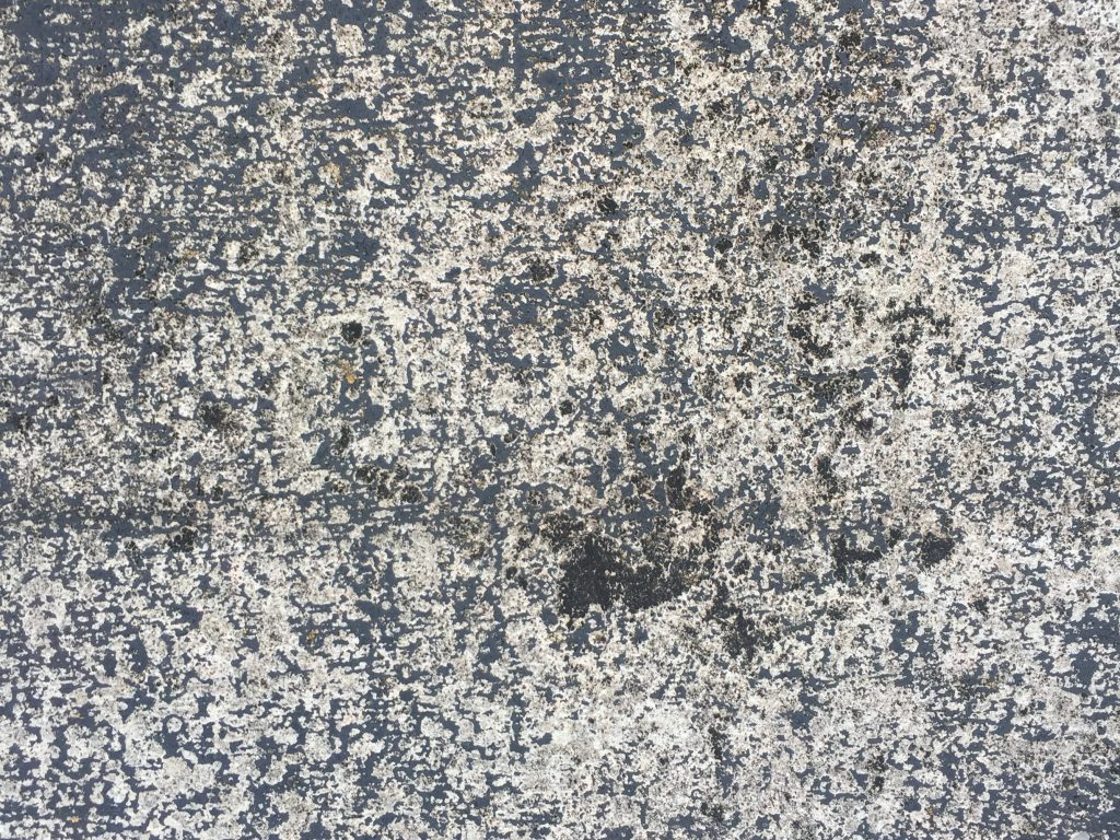 Cracked concrete with sparse black scuffs