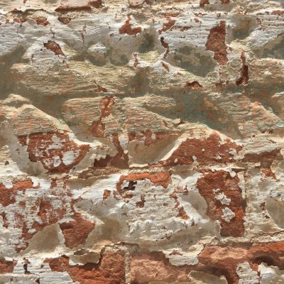 Cracking layers of thin white plaster over old bricks