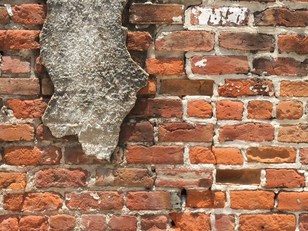 Cracked brick wall with chunk of concrete