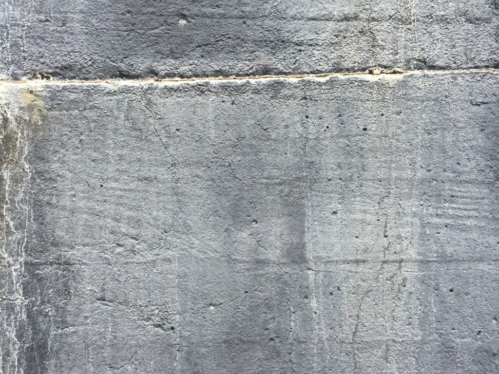 Medium grey concrete wall with streaks