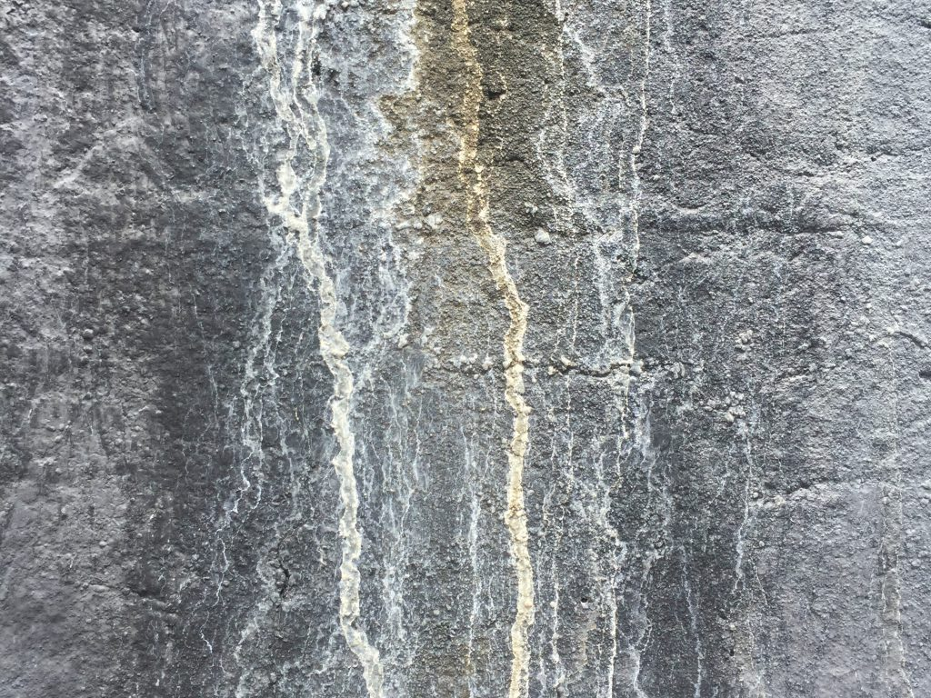 Charcoal grey stone wall with white drips