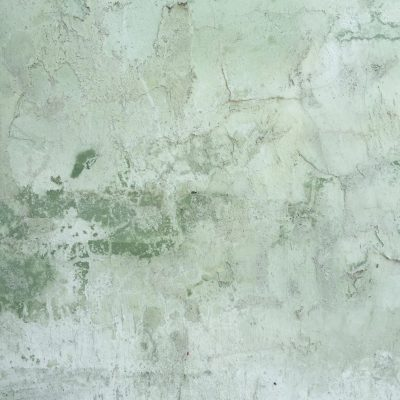 Green tinted layers of plaster cracking